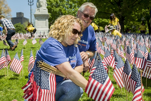 Volunteers sticking flags in the ground for Memorial Day Weekend