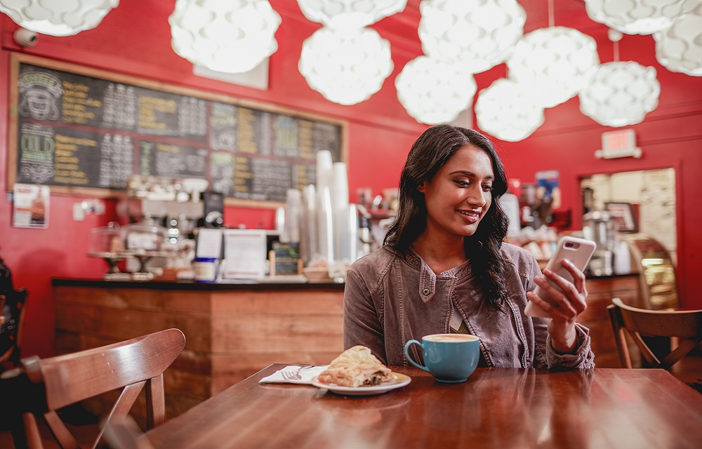 Woman in Cafe on Cell Phone using Eastern Mobile Banking