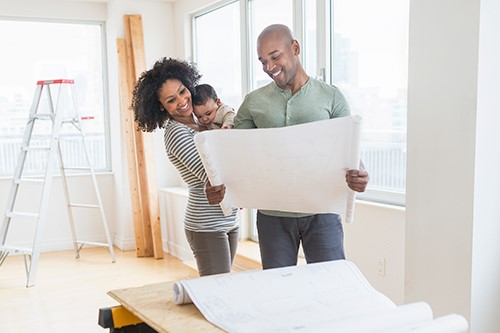 Couple with child looking at home renovation plans